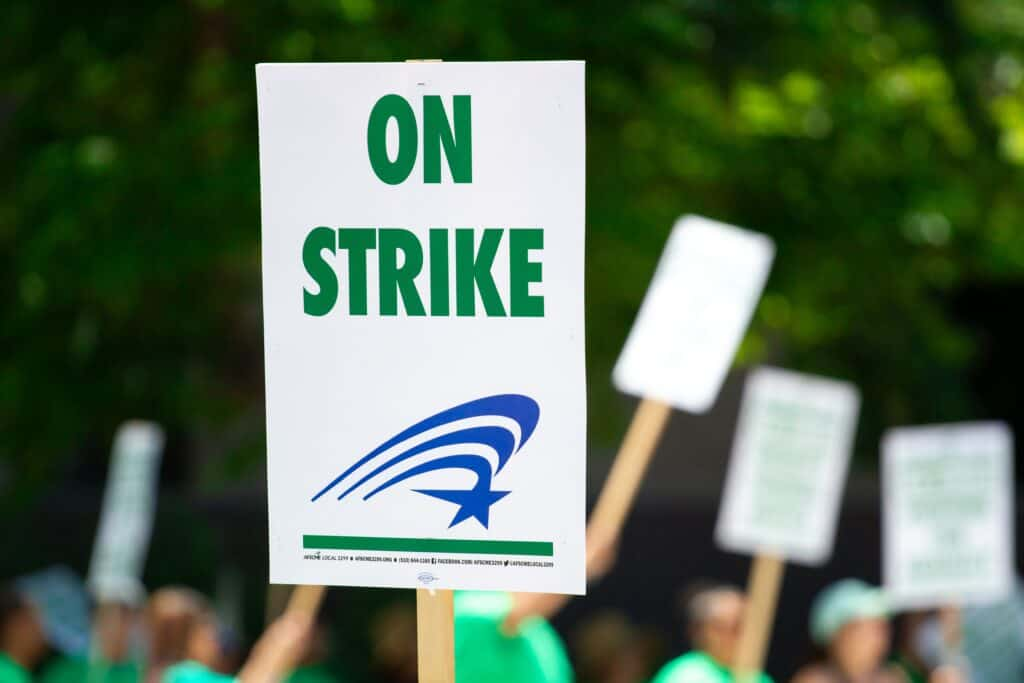 "A white sign with green words saying ""On Strike"" is held up in a strike protest."