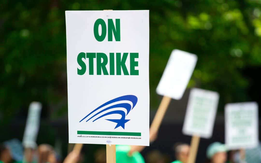 """A white sign with green words saying """"On Strike"""" is held up in a strike protest."""